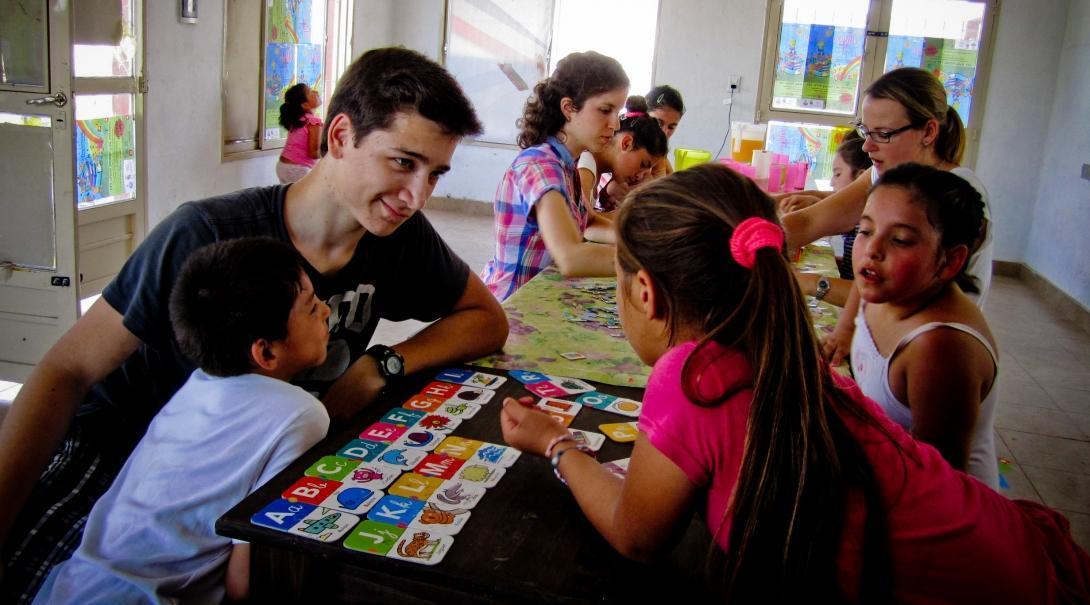 Voluntarios de enseñanza ayudando a los estudiantes a repasar el abecedario en inglés.